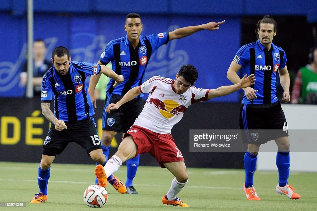 Kosuke Kimura #27 of the New York RedBulls and Andres Romero #15 of the Montreal Impact battle for the ball during the MLS game at the Olympic Stadium on April 5, 2014 in Montreal, Quebec, Canada.