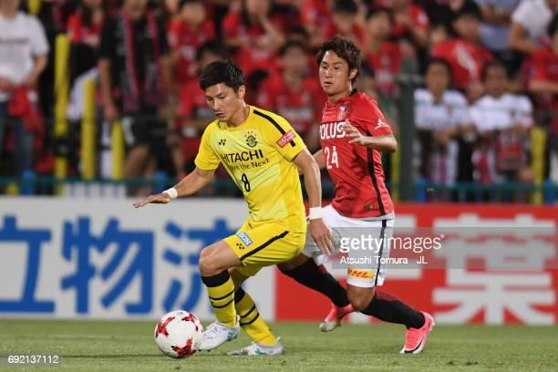 Kosuke Taketomi of Kashiwa Reysol controls the ball under pressure of Takahiro Sekine of Urawa Red Diamonds during the JLeague J1 match between...