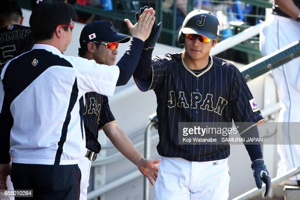 Kosuke Tanaka of Japan hits a single celerates after scoring in the top half of the eigth inning during the exhibition game between Japan and Chicago...