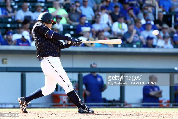 Kosuke Tanaka of Japan hits a single in the top half of the eigth inning during the exhibition game between Japan and Chicago Cubs at Sloan Park on...