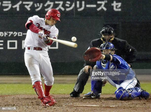 Kosuke Tanaka of the Hiroshima Carp breaks a scoreless tie with a tworun single in the fifth inning against the DeNA BayStars in Game 1 of the...