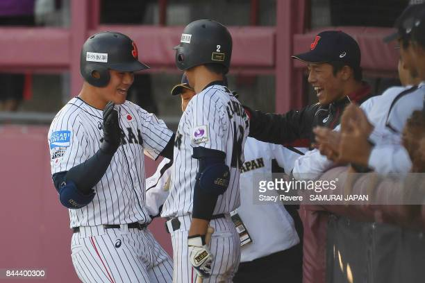 Kotaro Kiyomiya of Japan is congratulated by teammates following a solo home run during the fifth inning of a game against Canada during the WBSC U18...