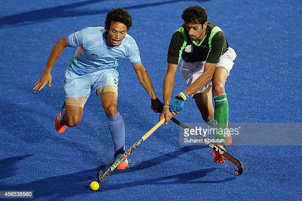 Kothajit Singh Khadangbam of India and Ahmad Shakeel Butt of Pakistan vie for the ball during the menÕs hockey gold medal match on day thirteen of...