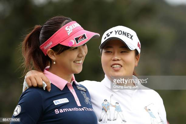 Kotono Kozuma of Japan talks with SunJu Ahn of South Korea on the 5th green in the second round during the TPoint Ladies Golf Tournament at the...