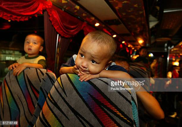 Kou Vang age3 watches TV onboard the bus taking the family to Bangkok on August 22 2004 in Wat Tham Krabok refugee camp in Tham Krabok Thailand...