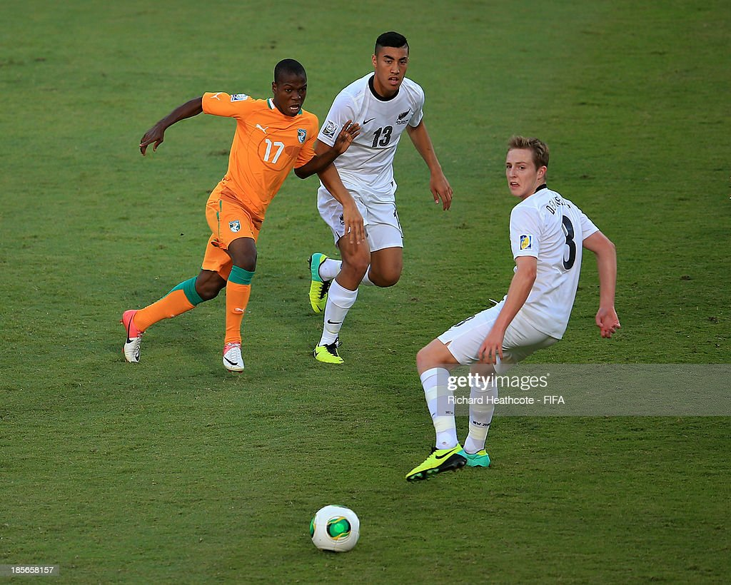 Kouame N'Guessan of Ivory Coast passes the ball past Spiros Agathos and Michael Den Heijer of New Zealand during the FIFA U-17 World Cup UAE 2013 Group B match between New Zealand and Ivory Coast at the Mohamed Bin Zayed Stadium on October 23, 2013 in Abu Dhabi, United Arab Emirates.