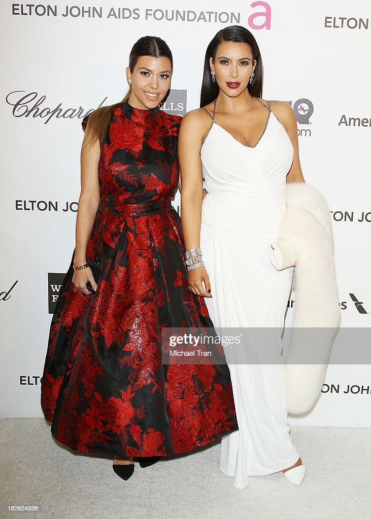 Kourtney Kardashian (L) and Kim Kardashian arrive at the 21st Annual Elton John AIDS Foundation Academy Awards viewing party held at West Hollywood Park on February 24, 2013 in West Hollywood, California.
