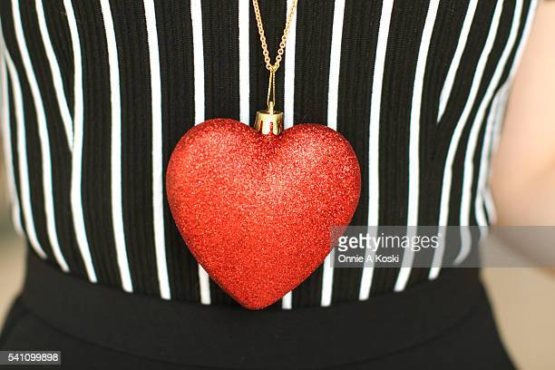 Kouta wearing Zoff eyeglasses a black and white vertical striped blouse an oversized chunky heart necklace a black midi skirt red suede ballet flats...