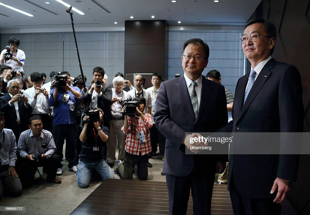 Kozo Takahashi, incoming president of Sharp Corp., right, and Takashi Okuda, incoming chairman, shake hands during a news conference in Tokyo, Japan, on Tuesday, May 14, 2013. Sharp Corp. forecast its first annual profit in three years as Japan's largest maker of liquid-crystal displays expects orders to recover after signing a deal with Samsung Electronics Co. Photographer: Tomohiro Ohsumi/Bloomberg via Getty Images
