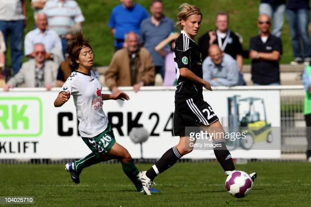 Kozue Ando of Duisburg challenges Saskia Bartusiak of Frankfurt during the Women's bundesliga match between FCR Duisburg and FFC Frankfurt at the...
