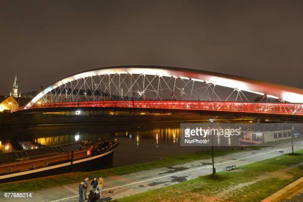 Krakow's landmark 'Kladka Bernatka' footbridge over Vistula river goes White and Red for Flag Day Flag Day was introduced to Poland in 2004 bridging...