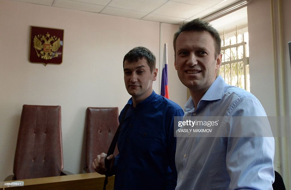 Kremlin critic and opposition leader Alexei Navalny (R) and his brother Oleg (L) stand in a courtroom in Moscow, on April 24, 2014. Along with his brother, Alexei Navalny went on trial today to face charges of stealing and laundering 27 million rubles ($756,500) from French cosmetics company Yves Rocher. AFP PHOTO / VASILY MAXIMOV