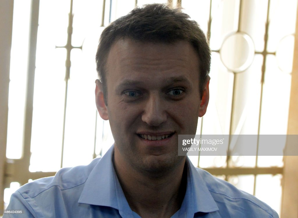 Kremlin critic and opposition leader Alexei Navalny smiles as he stands in a courtroom in Moscow, on April 24, 2014. Along with his brother Oleg, Alexei Navalny went on trial today to face charges of stealing and laundering 27 million rubles ($756,500) from French cosmetics company Yves Rocher. AFP PHOTO / VASILY MAXIMOV