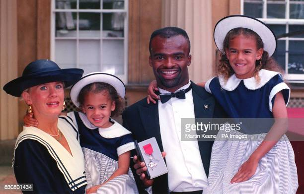 Kris Akabussi with his wife Monica and daughters Shakira 3 and Ashanti outside Buckingham Palace after he recieved his MBE from The Queen