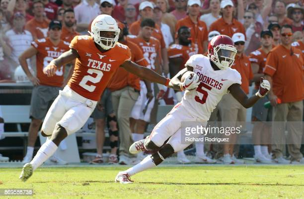 Kris Boyd of the Texas Longhorns pursues Marquise Brown of the Oklahoma Sooners in the second half of a football game at the Cotton Bowl on October...
