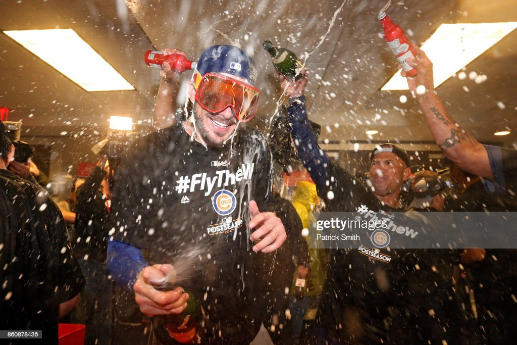 Kris Bryant #17 of the Chicago Cubs celebrates in the clubhouse with teammates after defeating the Washington Nationals 9-8 in game five of the National League Division Series at Nationals Park on October 13, 2017 in Washington, DC.