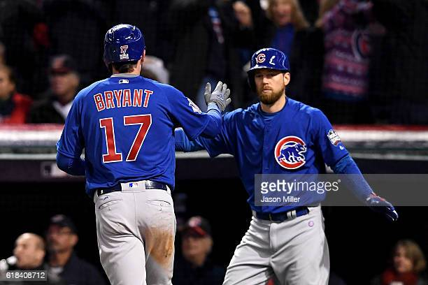 Kris Bryant of the Chicago Cubs celebrates with Ben Zobrist after scoring a run during the first inning against the Cleveland Indians in Game Two of...