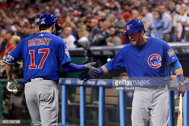 Kris Bryant of the Chicago Cubs celebrates with Ben Zobrist after hitting a solo home run during the first inning against the Cleveland Indians in...