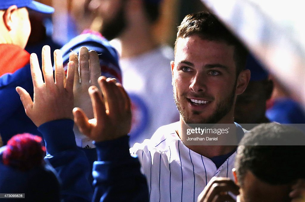 Kris Bryant #17 of the Chicago Cubs is congratulated in the dugout by teammates after hitting a solo home run in the 8th inning against the New York Mets at Wrigley Field on May 12, 2015 in Chicago, Illinois. The Cubs defeated the Mets 6-1.