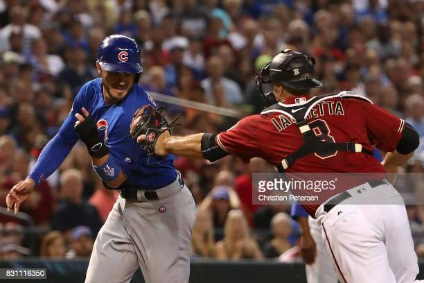 Kris Bryant of the Chicago Cubs is tagged out in a run down with catcher Chris Iannetta of the Arizona Diamondbacks during the third inning of the...