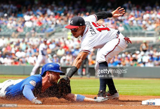 Kris Bryant of the Chicago Cubs is tagged out while trying to steal third base against Johan Camargo of the Atlanta Braves in the first inning at...