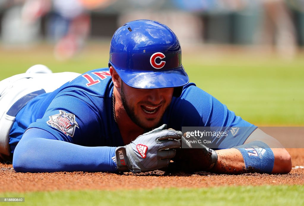 Kris Bryant #17 of the Chicago Cubs reacts as he holds his left hand after being tagged out while trying to steal third base against Johan Camargo #17 of the Atlanta Braves in the first inning at SunTrust Park on July 19, 2017 in Atlanta, Georgia.
