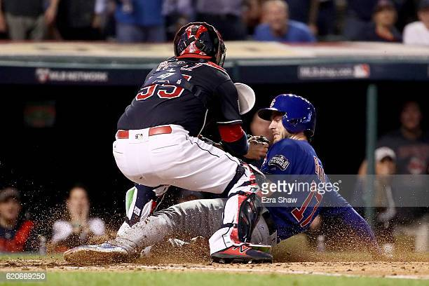Kris Bryant of the Chicago Cubs scores a run on a sacrifice fly ball hit by Addison Russell as Roberto Perez of the Cleveland Indians is unable to...