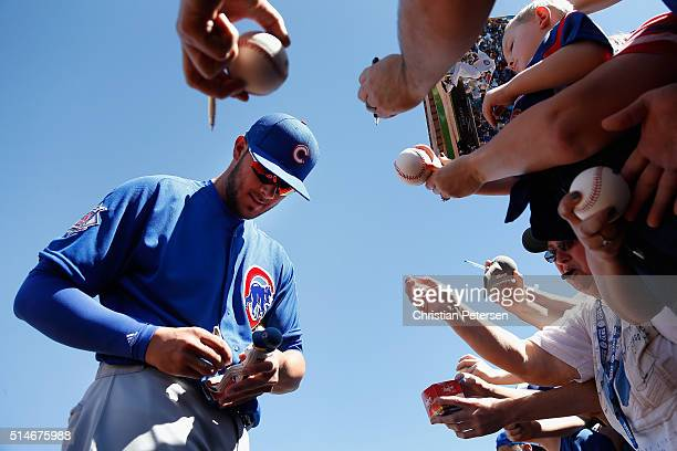 Kris Bryant of the Chicago Cubs signs autographs for fans before the spring training game against the Seattle Mariners at Peoria Stadium on March 10...