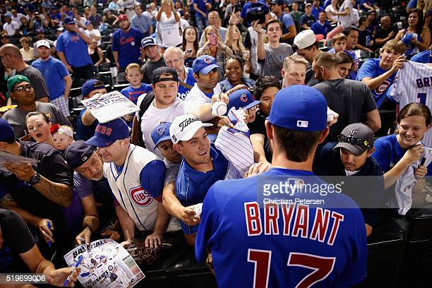 Kris Bryant of the Chicago Cubs signs autographs for fans before the MLB game against the Arizona Diamondbacks at Chase Field on April 7 2016 in...