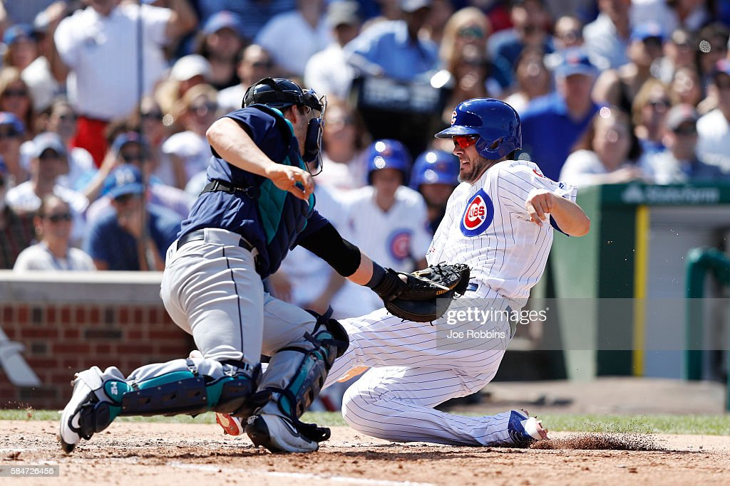 Kris Bryant #17 of the Chicago Cubs slides at home plate ahead of the tag by Mike Zunino #3 of the Seattle Mariners to score a run in the seventh inning at Wrigley Field on July 30, 2016 in Chicago, Illinois. The Mariners defeated the Cubs 4-1.