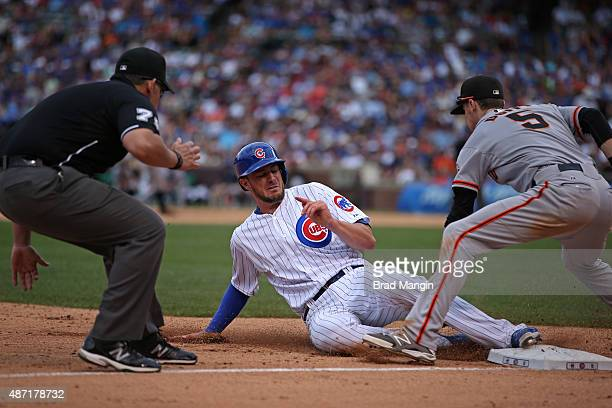 Kris Bryant of the Chicago Cubs slides safely into third base during the game against the San Francisco Giants as Giants third baseman Matt Duffy...