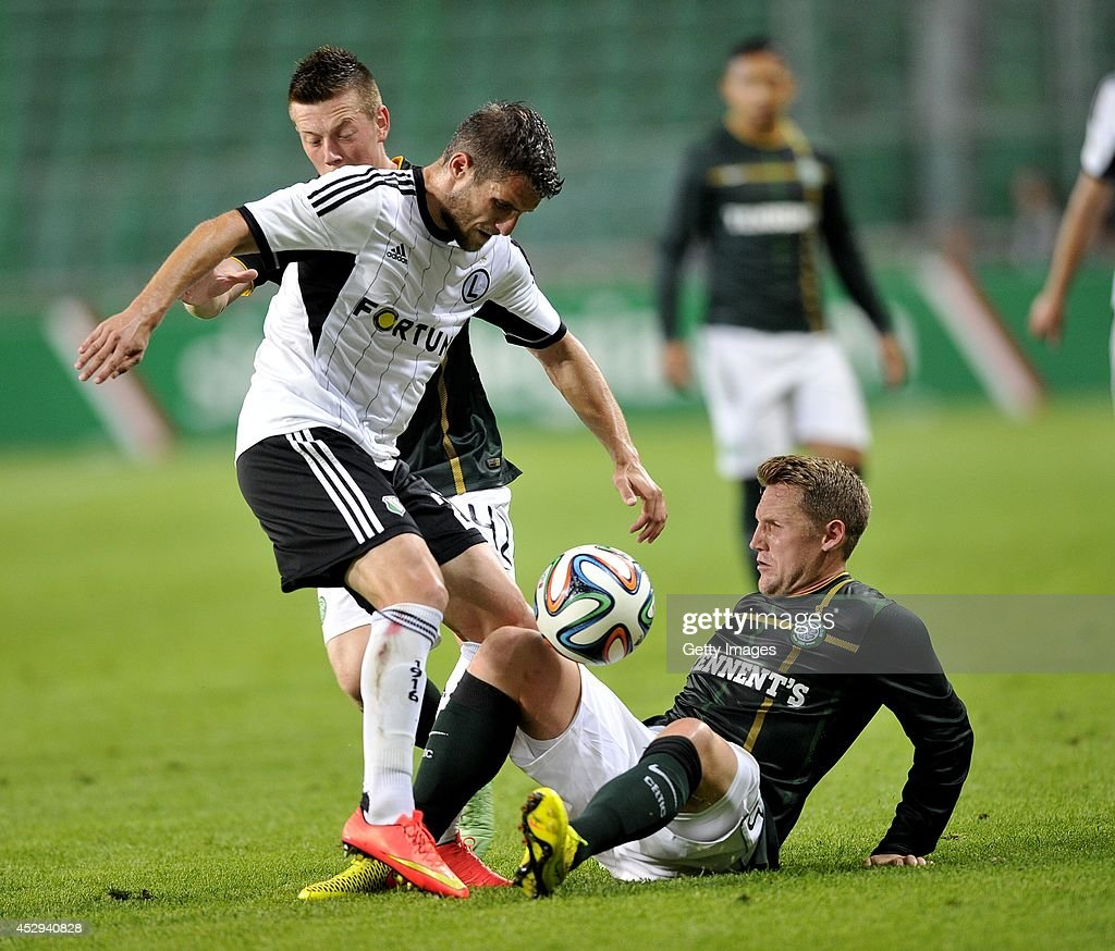 Kris Commons and Callum McGregor of Celtic fight for the ball with Lukasz Broz of Legia during the third qualifying round UEFA Champions League match between Legia and Celtic at Pepsi Arena on July 30, 2014 in Warsaw, Poland.