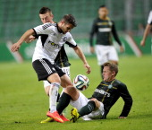 Kris Commons and Callum McGregor of Celtic fight for the ball with Lukasz Broz of Legia during the third qualifying round UEFA Champions League match...