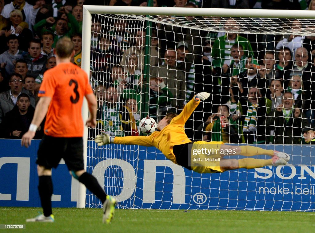 Kris Commons of Celtic puts the ball past Aleksandr Mokin of Shakhter Karagandy to score during the UEFA Champions League Play-off second leg match between Celtic and Shakhter Karagandy at Celtic Park on August 28, 2013 in Glasgow,Scotland.