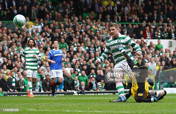 Kris Commons of Celtic scores the second goal past Rangers keeper Allan McGregor during the Clydesdale Bank Premier League match between Celtic and...