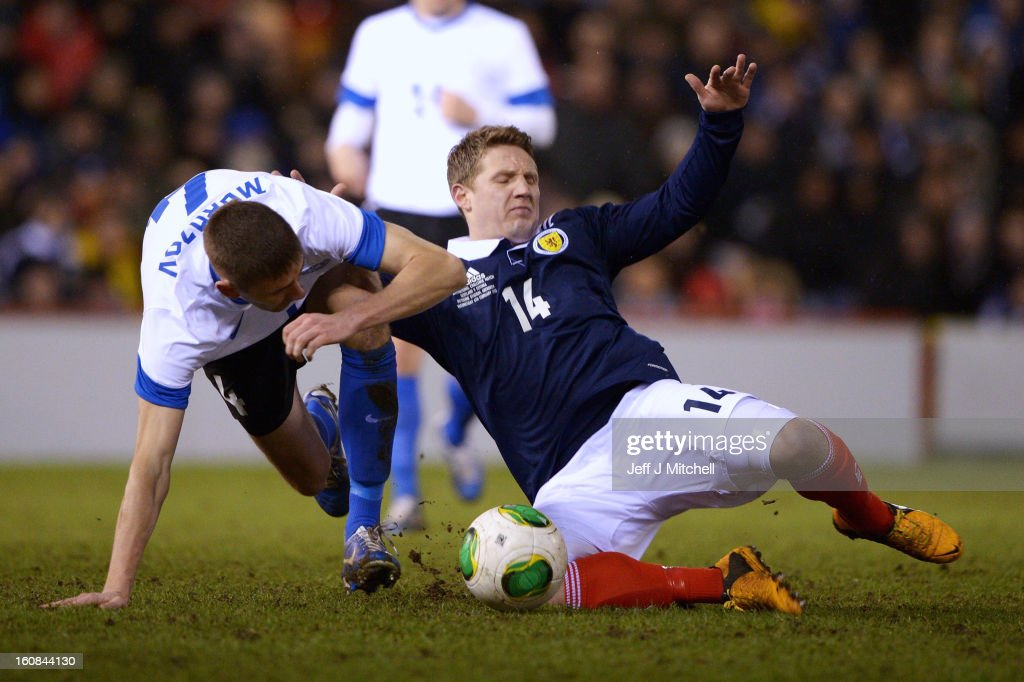 Kris Commons of Scotland tackles Igor Morozov of Estonia during the international friendly match between Scotland and Estonia at Pittodrie Stadium on February 6, 2013 in Aberdeen, Scotland.
