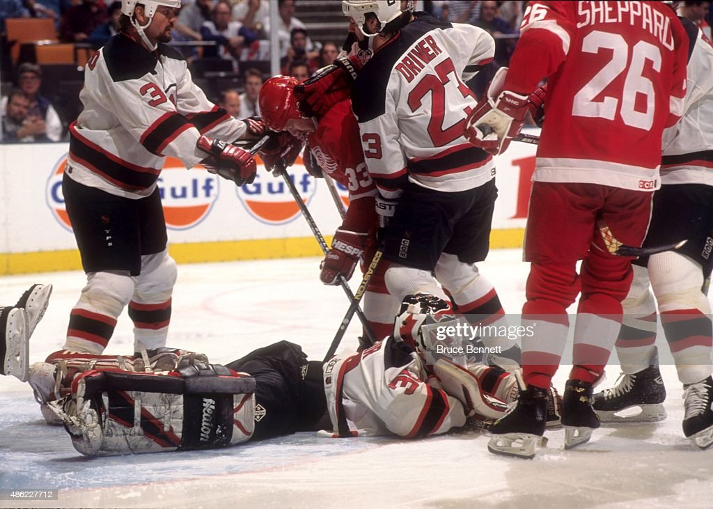 Kris Draper of the Detroit Red Wings goes for the puck as he is defended by Ken Daneyko and Bruce Driver of the New Jersey Devils as goalie Marin...