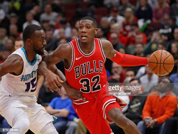 Kris Dunn of the Chicago Bulls moves against Kemba Walker of the Charlotte Hornets at the United Center on November 17 2017 in Chicago Illinois The...