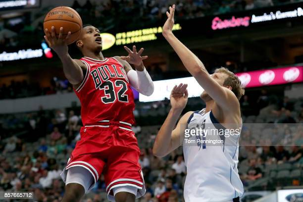 Kris Dunn of the Chicago Bulls shoots against Dirk Nowitzki of the Dallas Mavericks in the first half at American Airlines Center on October 4 2017...