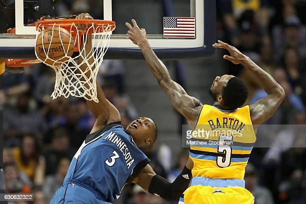 Kris Dunn of the Minnesota Timberwolves dunks the ball against Will Barton of the Denver Nuggets at the Pepsi Center on December 28 2016 in Denver...