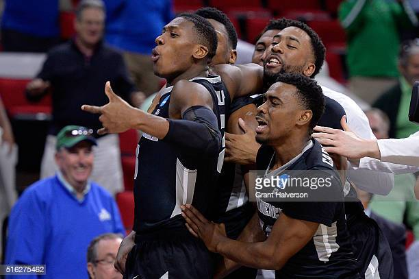 Kris Dunn of the Providence Friars celebrates with teammates Rodney Bullock and Kyron Cartwright after defeating the USC Trojans with a score of 70...