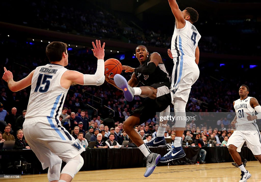 <a gi-track='captionPersonalityLinkClicked' href=/galleries/search?phrase=Kris+Dunn&family=editorial&specificpeople=7887137 ng-click='$event.stopPropagation()'>Kris Dunn</a> #3 of the Providence Friars drives to the basket against <a gi-track='captionPersonalityLinkClicked' href=/galleries/search?phrase=Darrun+Hilliard&family=editorial&specificpeople=8710176 ng-click='$event.stopPropagation()'>Darrun Hilliard</a> #4 and <a gi-track='captionPersonalityLinkClicked' href=/galleries/search?phrase=Ryan+Arcidiacono&family=editorial&specificpeople=7887112 ng-click='$event.stopPropagation()'>Ryan Arcidiacono</a> #15 of the Villanova Wildcats in the first half during a semifinal game of the Big East basketball tournament at Madison Square Garden on March 13, 2015 in New York City.