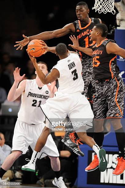 Kris Dunn of the Providence Friars tries to get a shot over Cheikh Mbodj and Jermaine Sanders of the Cincinnati Bearcats during a second round Big...
