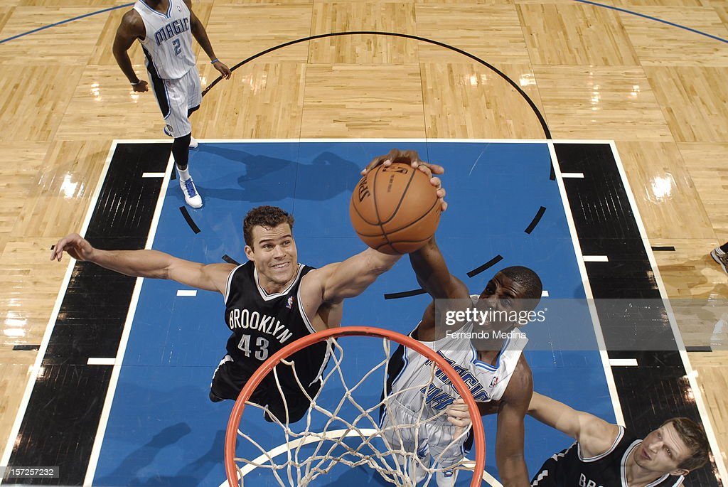 Kris Humphries #43 of the Brooklyn Nets against Andrew Nicholson #44 of the Orlando Magic fight for the ball in mid-air during the game on November 30, 2012 at Amway Center in Orlando, Florida.
