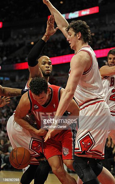 Kris Humphries of the New Jersey Nets looses control of the ball after being trapped by Taj Gibson Omer Asik and Kyle Korver of the Chicago Bulls at...
