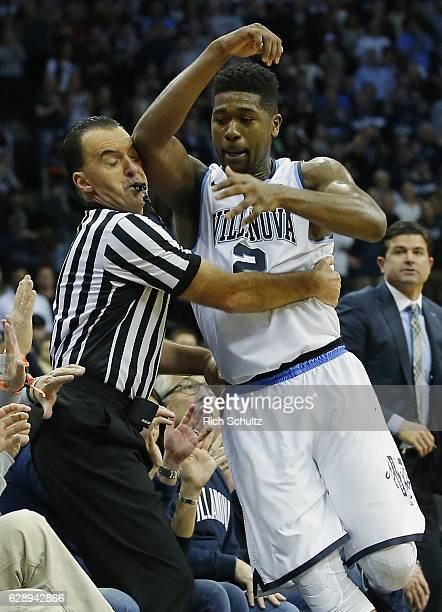 Kris Jenkins of the Villanova Wildcats attempts to keep the ball inbounds as he runs into the referee Roger Ayers during the second half of a college...