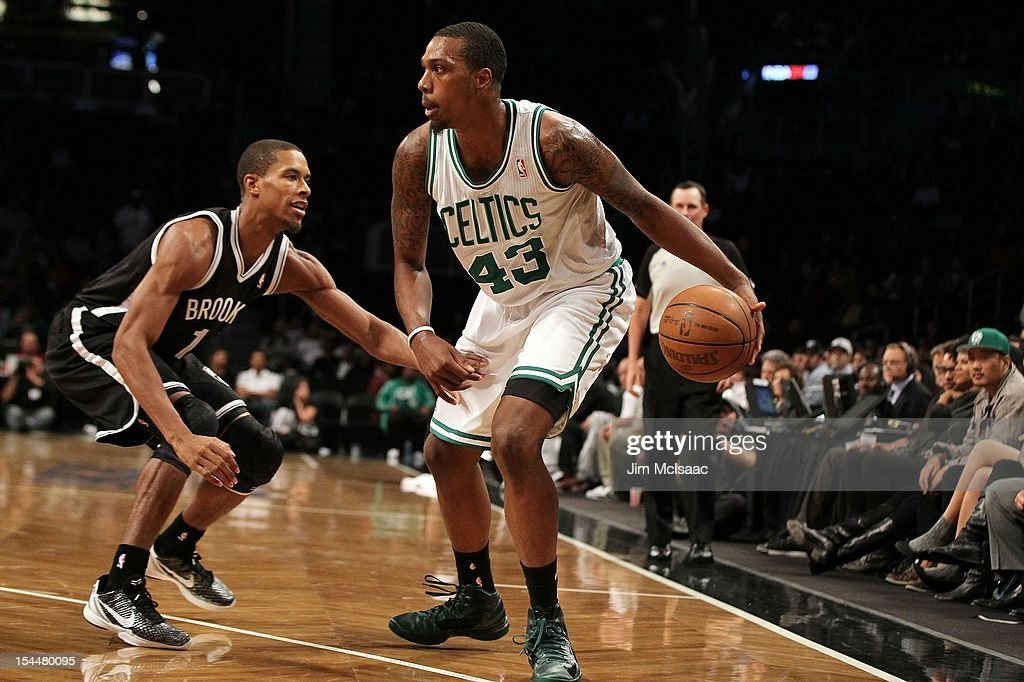 Kris Joseph of the Boston Celtics in action against Stephen Dennis of the Brooklyn Nets during a preseason game at the Barclays Center on October 18...