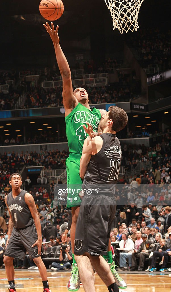 Kris Joseph of the Boston Celtics shoots against Tornike Shengelia of the Brooklyn Nets on December 25 2012 at the Barclays Center in Brooklyn New...