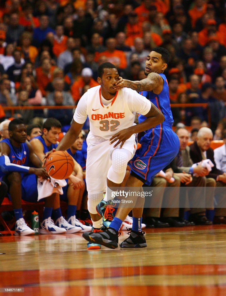 Kris Joseph of the Syracuse Orange is fouled by Mike Rosario of the Florida Gators during the game at the Carrier Dome on December 2 2011 in Syracuse...
