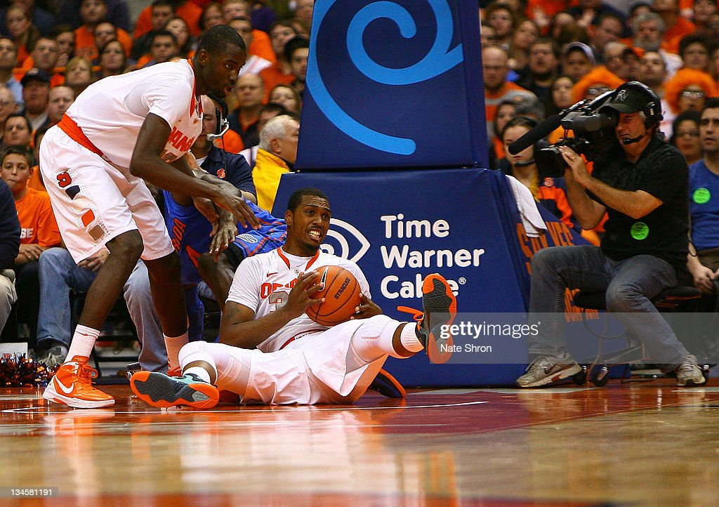 Kris Joseph of the Syracuse Orange looks to pass from the floor as teammate Baye Keita looks on in the game against the Florida Gators at the Carrier...